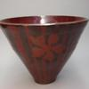 Thrown bowl decorated with black slip and red glaze
