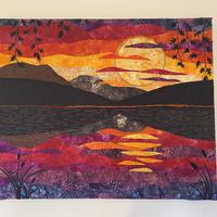 Quilted sunset with free motion embroidery and appliquestretched over canvas
