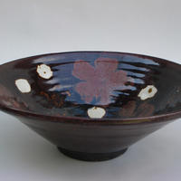 Profile view of the stoneware bowl with red flowers