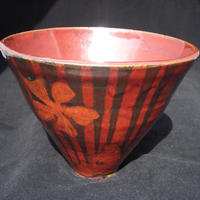 Red and black bowl with flowers and stripes