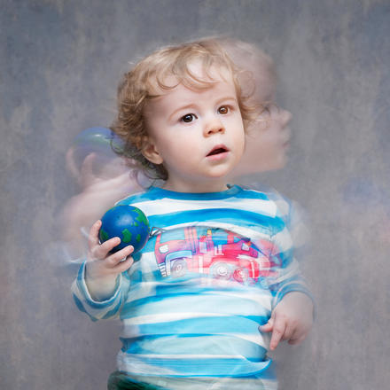 Moving portrait of a young child in striped shirt and holding a ball to throw